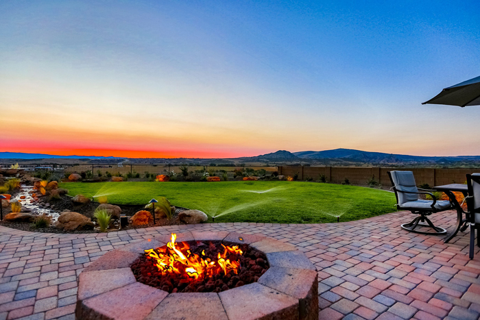 The flicker of the flame draws people to family and friendship around a firepit.